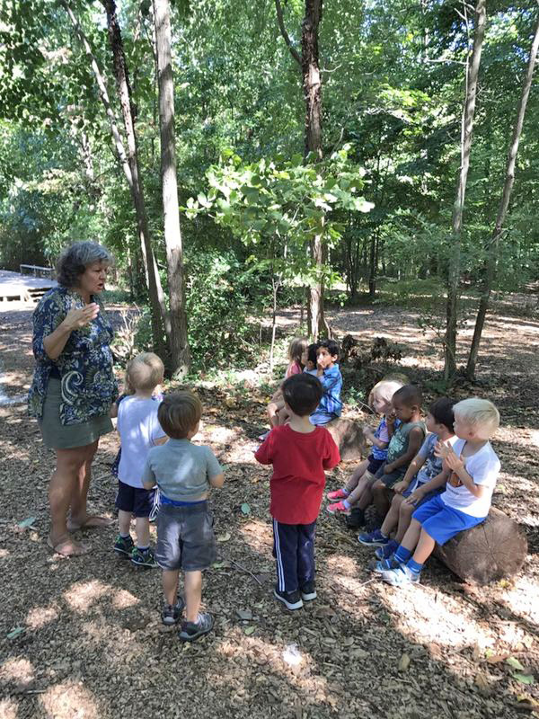 teacher with students in woods